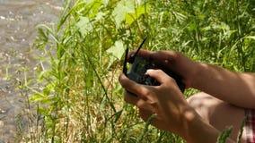 Les mains en gros plan de types utilisant à télécommande avec le bourdon ont monté l'appareil-photo, fond de rivière de montagne  banque de vidéos