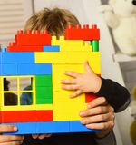 Les mains et l'enfant masculins tiennent la construction en briques colorée de jouet image libre de droits