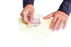 Les mains et l'enveloppe avec encaissent dedans la banque thaïlandaise Image libre de droits