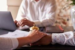 Les mains ethniques multi de prise de couples à l'hôtel signent le bureau, détail Photographie stock