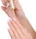 Les mains femelles appliquant le clou disparaissent sur l'ongle Photo libre de droits