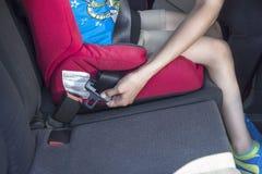 Les mains femelles attachent la ceinture de sécurité L'enfant s'assied dans un siège de voiture image stock