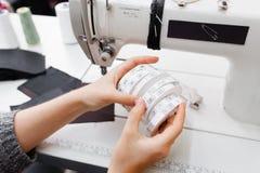 Les mains femelles avec des rouleaux de taille étiquettent pour des vêtements Photos libres de droits