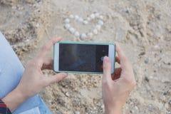 Les mains femelles avec des smartphones prennent des photos des coquilles sur le sable sous forme de coeur photographie stock libre de droits