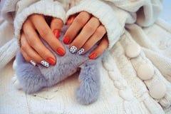 Les mains femelles avec la belle conception des clous tiennent un jouet sur un knit photos stock