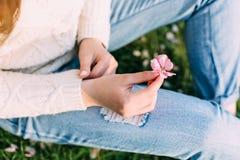 Les mains femelles avec la manucure neutre tenant un pommier dentellent la fleur Dehors, ressort Images libres de droits