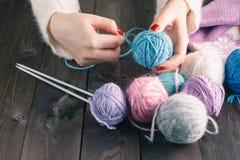 Les mains femelles avec la manucure pourpre sont les rais tricotés en métal d'a image libre de droits