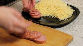 Les mains femelles décalent la saucisse coupée en tranches à un plat au fromage râpé Préparation de pizza banque de vidéos