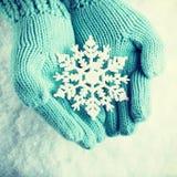 Les mains femelles dans la sarcelle d'hiver légère ont tricoté des mitaines avec le flocon de neige merveilleux de scintillement Images stock