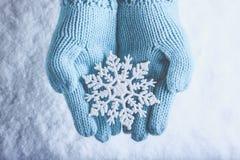 Les mains femelles dans la sarcelle d'hiver légère ont tricoté des mitaines avec le flocon de neige merveilleux de scintillement  Images libres de droits