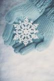 Les mains femelles dans la sarcelle d'hiver légère ont tricoté des mitaines avec le flocon de neige merveilleux de scintillement  Photographie stock