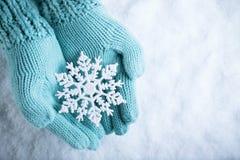 Les mains femelles dans la sarcelle d'hiver légère ont tricoté des mitaines avec le flocon de neige merveilleux de scintillement  Image stock
