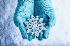 Les mains femelles dans la sarcelle d'hiver légère ont tricoté des mitaines avec le flocon de neige merveilleux de scintillement  Photo stock