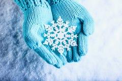 Les mains femelles dans la sarcelle d'hiver légère ont tricoté des mitaines avec le flocon de neige merveilleux de scintillement  Photos stock