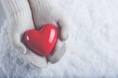 Les mains femelles dans le blanc ont tricoté des mitaines avec un coeur rouge brillant sur un fond de neige Concept d'amour et de Photo libre de droits