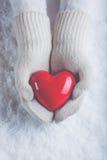 Les mains femelles dans le blanc ont tricoté des mitaines avec un coeur rouge brillant sur un fond de neige Concept d'amour et de Photos libres de droits