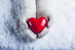 Les mains femelles dans le blanc ont tricoté des mitaines avec un coeur rouge brillant sur un fond de neige Concept d'amour et de Images libres de droits