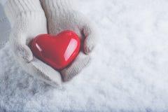 Les mains femelles dans le blanc ont tricoté des mitaines avec un coeur rouge brillant sur un fond de neige Concept d'amour et de Photographie stock