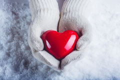 Les mains femelles dans le blanc ont tricoté des mitaines avec un coeur rouge brillant sur un fond de neige Concept d'amour et de Photos stock