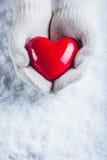 Les mains femelles dans le blanc ont tricoté des mitaines avec un coeur rouge brillant sur un fond de neige Concept d'amour et de Photographie stock libre de droits