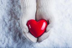 Les mains femelles dans le blanc ont tricoté des mitaines avec un coeur rouge brillant sur un fond de neige Concept d'amour et de Photo stock