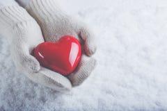 Les mains femelles dans le blanc ont tricoté des mitaines avec un coeur rouge brillant sur un fond de neige Concept d'amour et de Image libre de droits