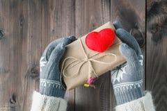 Les mains femelles dans le gant donnent l'amour actuel Photographie stock libre de droits