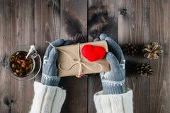 Les mains femelles dans le gant donnent l'amour actuel Photographie stock