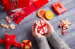 Les mains femelles dans le gris ont tricoté le chandail tenant le boîte-cadeau sur Christm Photographie stock libre de droits