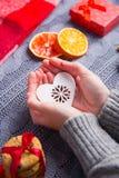Les mains femelles dans le gris ont tricoté le chandail tenant le coeur sur Noël Images stock