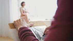 Les mains femelles dessine des croquis dans le studio de dessin avec le modèle nu clips vidéos
