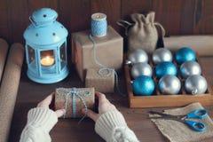 Les mains femelles emballent un cadeau de Noël sur une table en bois Photos stock