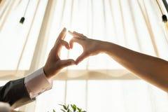 Les mains femelles et masculines formant un coeur forment avec la lumière du soleil à l'intérieur de restaurant Concept de l'amou Photos stock