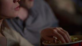 Les mains femelles et masculines prennent le maïs éclaté du seau de papier Manger du maïs de bruit au cinéma banque de vidéos