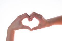 Les mains femelles faisant le coeur forment le symbole pour l'amour d'isolement sur le petit morceau image stock