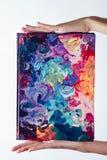 Les mains femelles hautes étroites de macro tiennent le carnet avec de la peinture à l'huile différente de couleur acrylique colo photos libres de droits