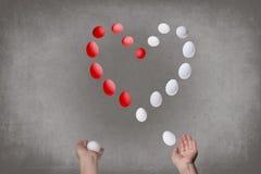 Les mains femelles jonglent des oeufs sous forme de coeur du ` s de Valentine Concept de nourriture Photos libres de droits