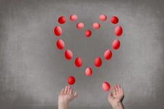 Les mains femelles jonglent des oeufs sous forme de coeur du ` s de Valentine Concept de nourriture Images stock