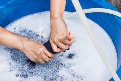 Les mains femelles lavent l'habillement à la main avec le détergent en bassin Sele images stock