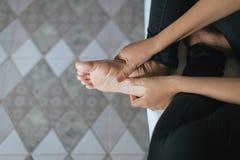 Les mains femelles lui donnant le massage paye dans la chambre à coucher, massage de semelles de pied Image stock
