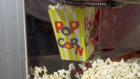 Les mains femelles met le maïs éclaté dans le sac de papier Vente du maïs éclaté sur la rue Tir de cardan banque de vidéos