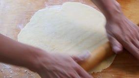 Les mains femelles ont arrosé la pâte de farine et de roulement pour la pâtisserie banque de vidéos
