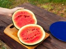 Les mains femelles ont coupé une pastèque mûre sur une table en bois avec un couteau image stock