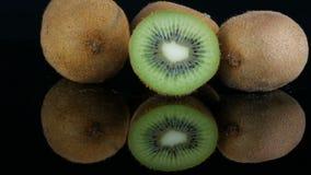 Les mains femelles ont mis le fruit coupé mûr à côté du kiwi entier sur la surface de miroir sur un fond noir dans le studio clips vidéos