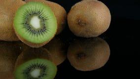 Les mains femelles ont mis le fruit coupé mûr à côté du kiwi entier sur la surface de miroir sur un fond noir dans le studio banque de vidéos