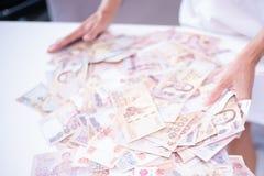 Les mains femelles rassemblent beaucoup d'argent sur une table blanche, billets de banque tha?landais, billets de banque russes images stock