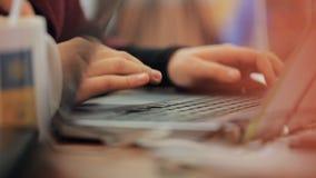 Les mains femelles se déplacent sur le touchpad sur l'ordinateur portable, un groupe d'étudiants de troisième cycle établiront un clips vidéos