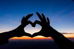Les mains femelles sous forme de coeur contre le ciel passent des faisceaux du soleil Mains dans la forme du coeur d'amour Images libres de droits