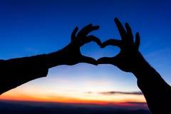 Les mains femelles sous forme de coeur contre le ciel passent des faisceaux du soleil Mains dans la forme du coeur d'amour Image libre de droits