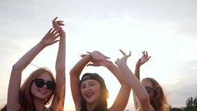 Les mains femelles sur le crépuscule de fond, été, meilleurs amis heureux dansant dans le coucher du soleil sur la plage, amies s banque de vidéos